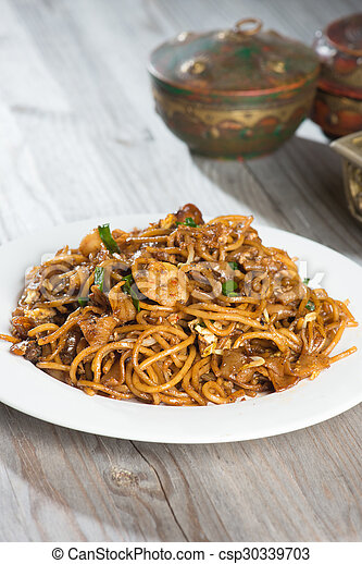 Fried Penang Char Kuey Teow which is a popular noodle dish in Malaysia, Indonesia, Brunei and Singapore - csp30339703