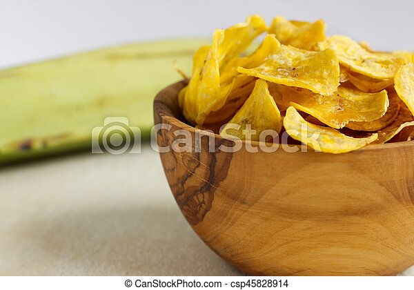 Fried plantain chips in a wooden bowl. - csp45828914