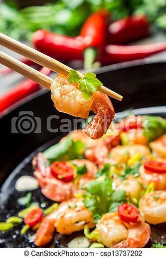 Fried shrimp on chopsticks with herbs - csp13737202