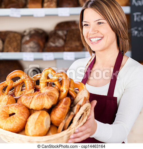 Friendly bakery assistant with a basket of rolls - csp14463164