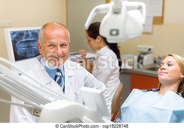 Friendly dentist with female patient dental office - csp18228748