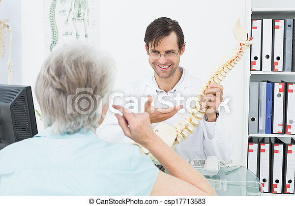 Friendly doctor explaining spine to - csp17713583