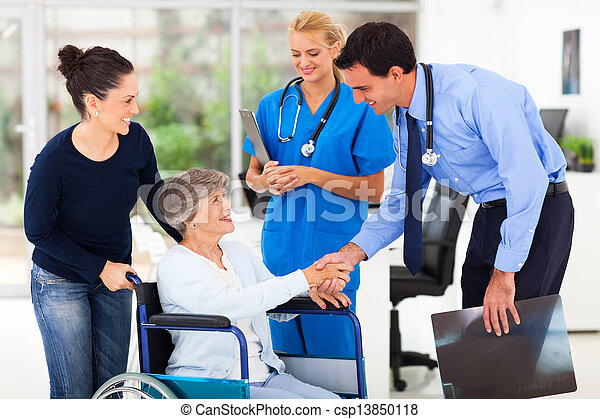 friendly medical doctor greeting senior patient - csp13850118