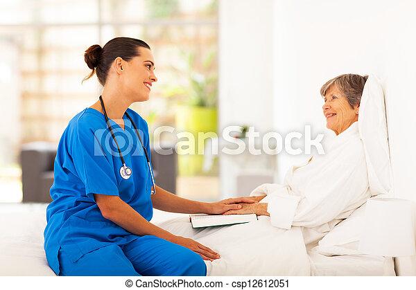 friendly nurse visiting senior patient - csp12612051