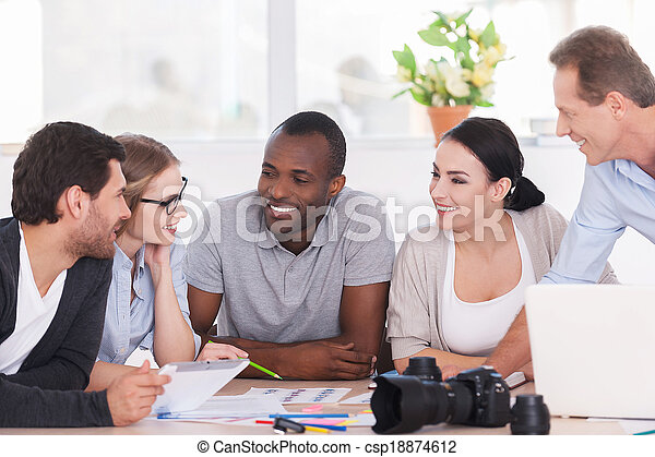 Friendly office discussion. Group of cheerful business people sitting together at the table and discussing something - csp18874612