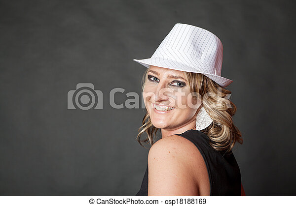 Friendly smiling young adult woman wearing white pinstripe hat - csp18188169