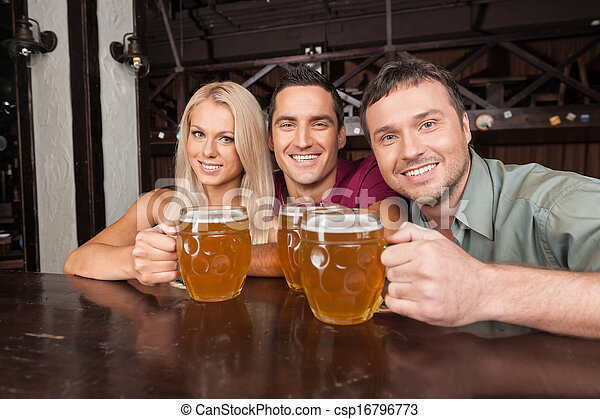 Friends at the bar. Two cheerful young men and beautiful young women looking at camera and smiling while holding glasses with beer - csp16796773