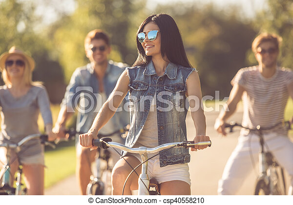 Friends cycling in park - csp40558210