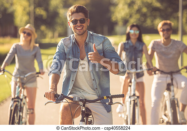 Friends cycling in park - csp40558224