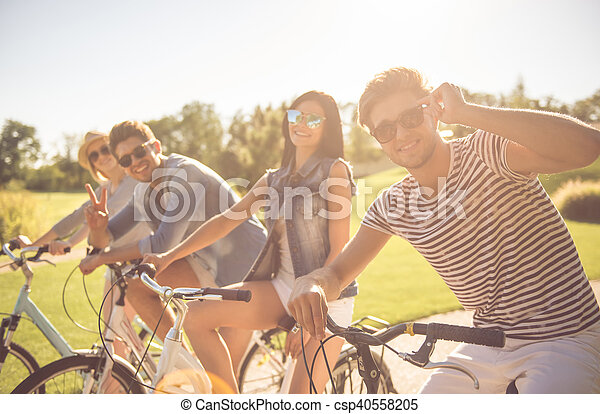 Friends cycling in park - csp40558205