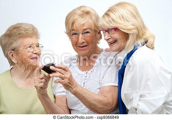 Alte Freundinnen mit mobilem Gerät. - csp9366849