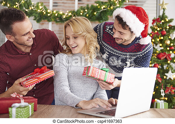 Friends Handing Over Christmas Presents To Each Other