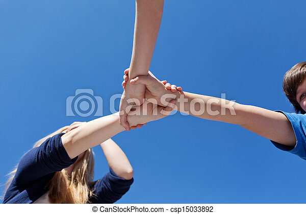 Friends Holding Hands Against Clear Blue Sky - csp15033892