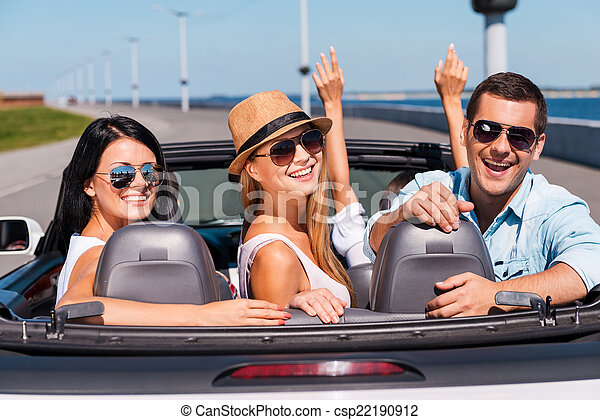 Friends in convertible. Group of young happy people enjoying road trip in their convertible while three of them looking over shoulder and smiling - csp22190912