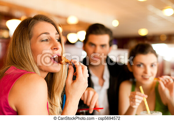 Friends in Restaurant eating fast food - csp5694572