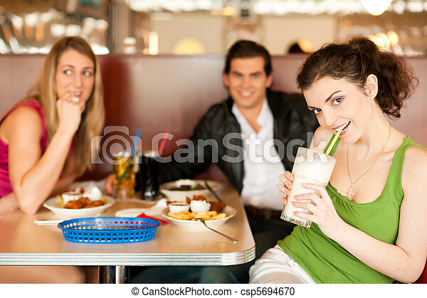 Friends in Restaurant eating fast food - csp5694670