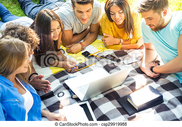 Friends looking at laptop outdoors - csp29919988
