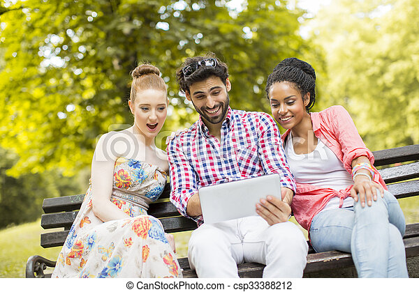 Friends on the bench with tablet - csp33388212