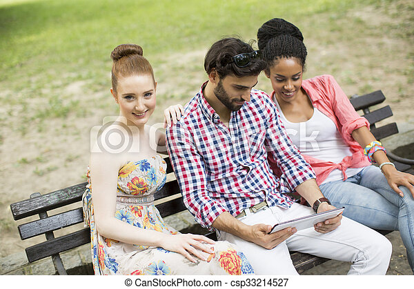 Friends on the bench with tablet - csp33214527
