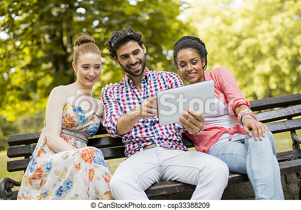 Friends on the bench with tablet - csp33388209