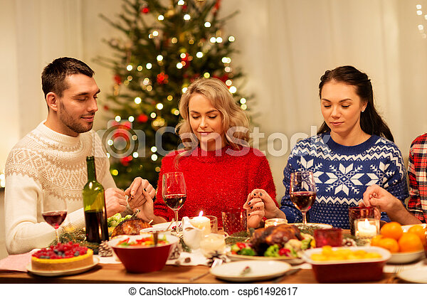 Christmas Dinner Prayer.Friends Praying Before Christmas Dinner At Home