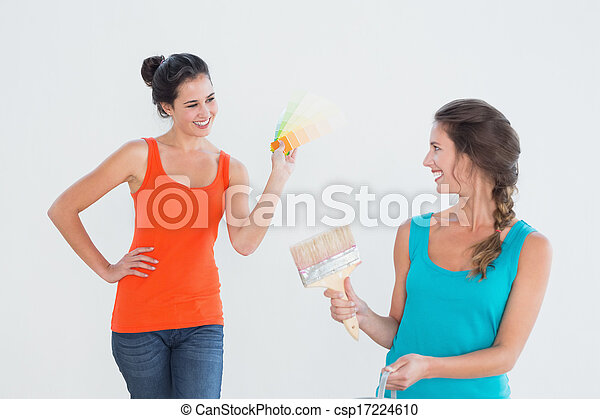 Friends with paint brush choosing color for painting a room - csp17224610