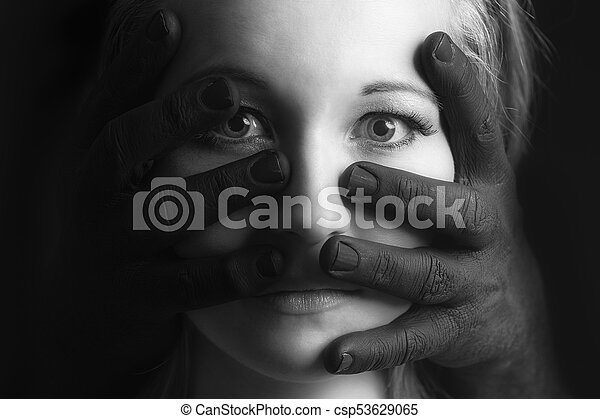 Frightened blonde woman grabbed by black hands on her face artistic conversion - csp53629065
