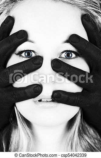 Frightened blonde woman grabbed by black hands on her face artistic conversion - csp54042339