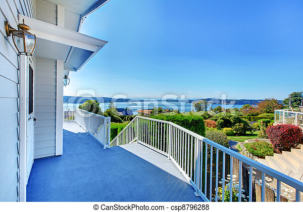 Front door porch with water view and grey house and bush greenery. - csp8796288