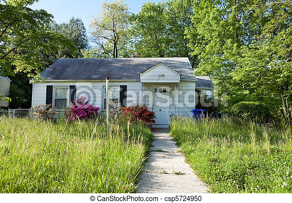 Front View Abandoned Foreclosed Cape Cod Home Long Grass - csp5724950