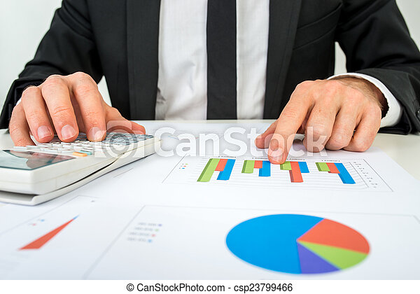 Front view of the hands of a accountant analysing a bar graph - csp23799466