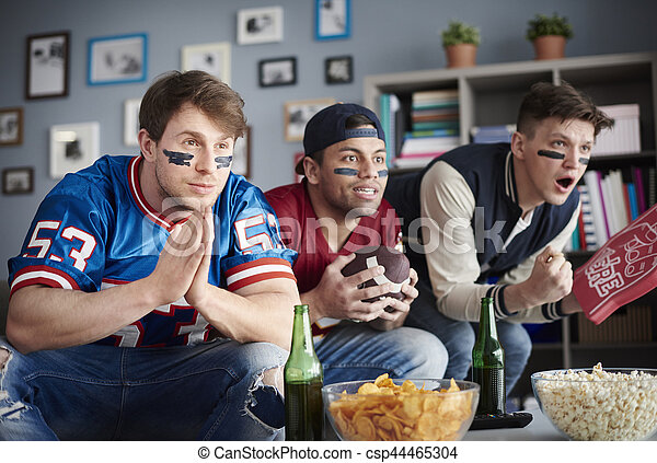 Front view of three men watching American football - csp44465304