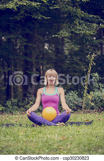 Front view of young blonde woman making a Lotus position in cross-legged - csp30230823