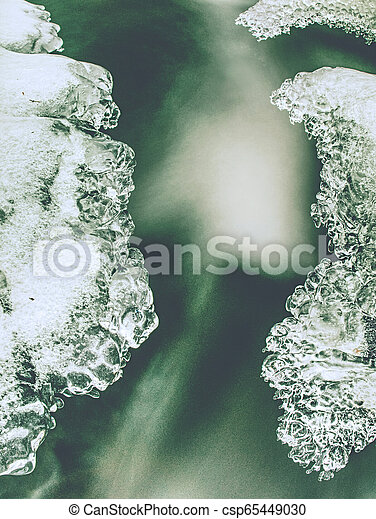 Frozen small waterfall. Detail of rounded icicles - csp65449030