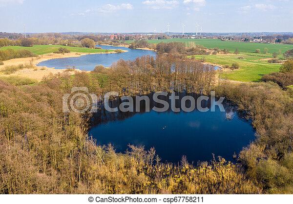 Drohnenfoto einer grünen Seelandschaft im Frühjahr - csp67758211