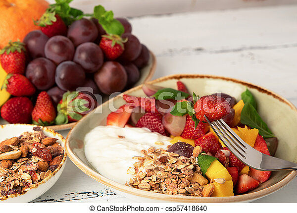 Fruit berry salad with yogurt and granola for healthy breakfast - csp57418640