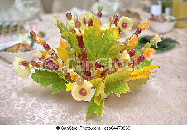 Fruit bouquet with autumn leaves, close-up - csp64479369