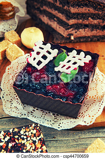 fruit dessert with black currant, brown form , decorated with chocolate, cinnamon, anise, - csp44700659