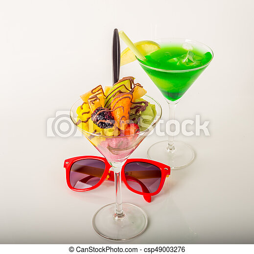 Fruit ice cream, decorated with fresh fruit, chocolate covered, green drink, martini glass, sunglasses - csp49003276