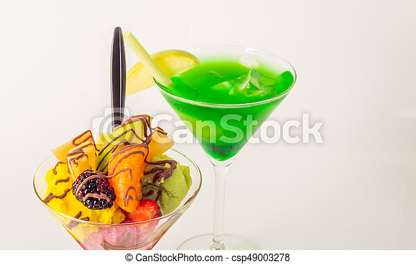 Fruit ice cream, decorated with fresh fruit, chocolate covered, green drink, martini glass - csp49003278