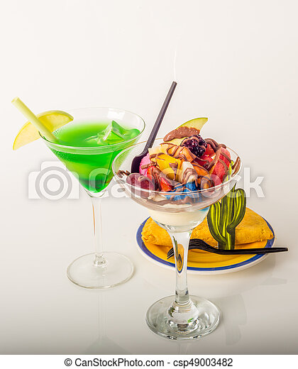 Fruit ice cream, decorated with fresh fruit, chocolate covered, green drink, martini glass, jamaican food - csp49003482