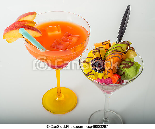 Fruit ice cream, decorated with fresh fruit, chocolate covered, orange drink, margarita glass - csp49003297