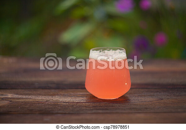 Fruit juice in a crystal glass on wooden table - csp78978851