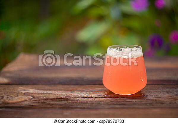 Fruit juice in a crystal glass on wooden table - csp79370733