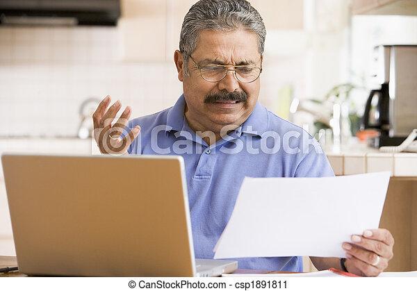 Mann in der Küche mit Laptop und Papierkram frustriert - csp1891811