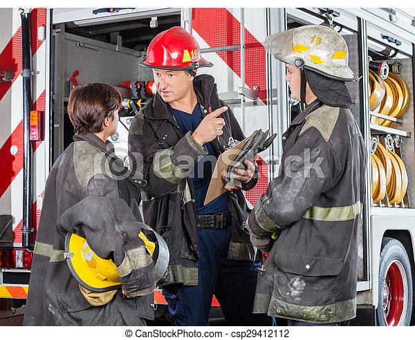 Bombero discutiendo con colegas en la estación de bomberos - csp29412112