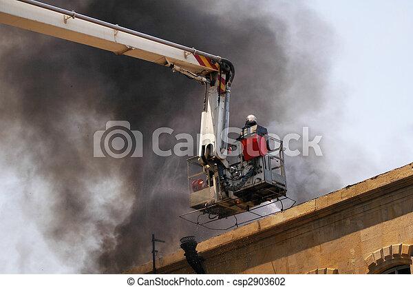 Bomberos en el boom del camión de bomberos durante el incendio - csp2903602