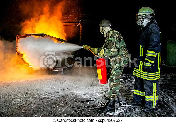Bomberos entrenando para combatir fuego. - csp64267627