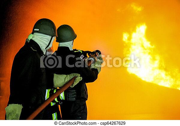 Bomberos entrenando para combatir fuego. - csp64267629