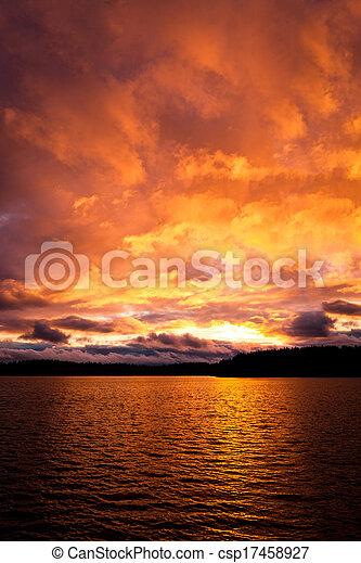 Fuego dramático, atardecer rojo sobre un lago - csp17458927